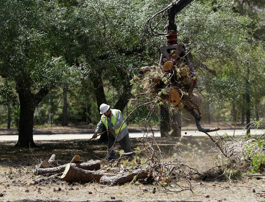 A  City of Houston worker cleans up a dead tree at Memorial Park Friday. (KAREN WARREN: CHRONICLE) Photo: Karen Warren / © 2011 Houston Chronicle