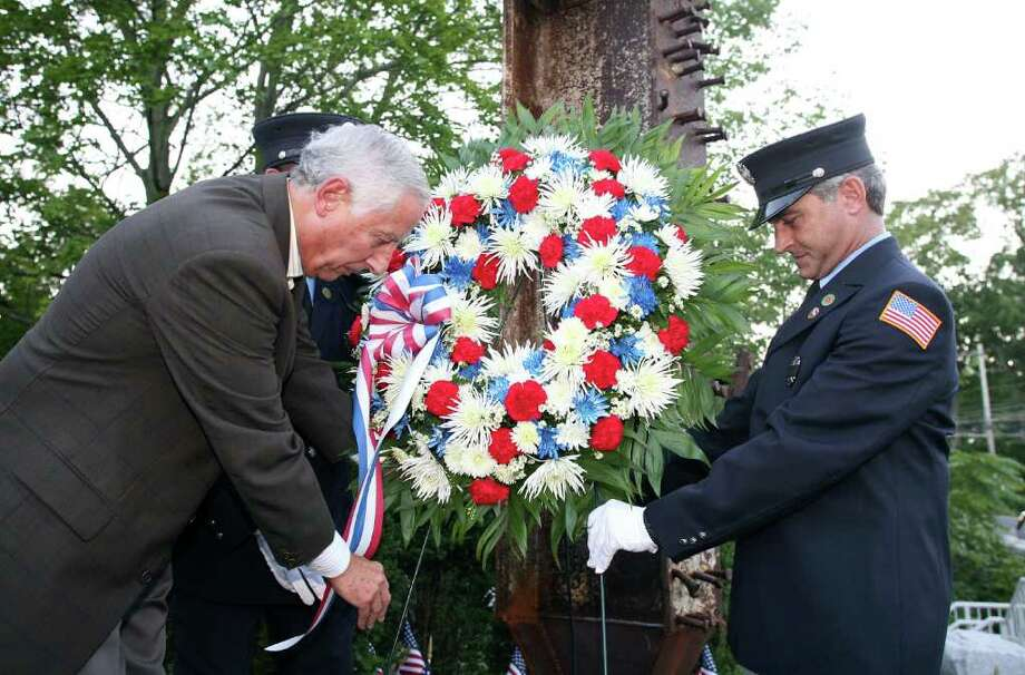 Ralph Sabbag, left, helps lay a wreath at the base of an 8-foot piece of steel from the former World Trade Center site during a ceremony Friday evening, Sept. 9, 2011, at the Glenville Fire Company.  Sabbag's son, Jason, perished in the Sept. 11 terrorist attacks. Photo: David Ames / Greenwich Time