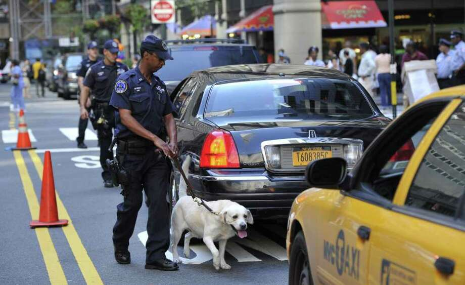 A canine unit police officer inspects cars outside the Grand Central Station in New York on September 09, 2011. Security measures around the city were increased two days before the tenth anniversary of the 9/11 attacks against the World Trade Center in New York. Traffic clogged up at police checkpoints Friday in New York and police with bomb sniffer dogs patrolled rail stations as US officials warned about an unconfirmed, but credible terrorism threat. Photo: MLADEN ANTONOV, Getty / AFP