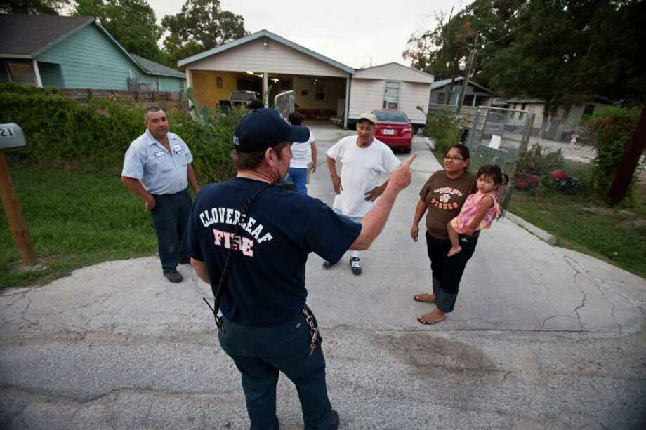 After a canceled evacuation, Ronald Doyal, of the Cloverleaf Fire Department, speaks to neighbors near the northwest corner of East Sam Houston Parkway and the East Freeway on Friday. Photo: Eric Kayne, For The Chronicle / © 2011 Eric Kayne