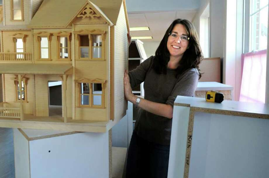 Susie Vallon, owner of Whimsies, is moving from 18 Lewis Street in Greenwich to 39 Lewis Street, holds one of her doll houses in the new store on Tuesday, Aug. 30, 2011.Susie Vallon, owner of Whimsies, is moving from Lewis 18 St., to  39 Lewis St., in the rear, in Greenwich. Vallon stands with one of her doll houses while she prepares her new store on Tuesday, Aug. 30, 2011. Photo: Helen Neafsey / Greenwich Time