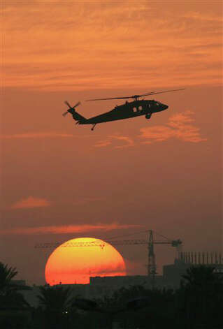 FILE - In this Nov. 14, 2006 file photo, the sun sets as a Black Hawk helicopter hovers over Baghdad's protected Green Zone.  America's wars since the attacks of Sept. 11, 2001 have been a boon for the maker of Black Hawks. Sales at the Stratford, Conn.-based Sikorsky Aircraft Corp., more than doubled in five years, to $6.7 billion in 2010, due in large part to the companyís military business that includes the Black Hawk. (AP Photo/Darko Bandic, File) Photo: Darko Bandic, AP / AP2006