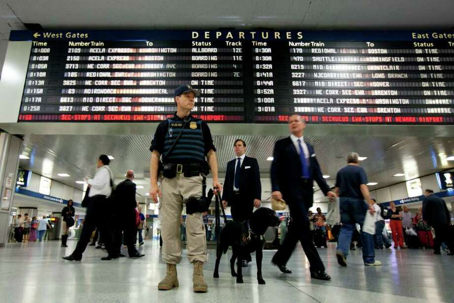 An Amtrack K-9 division police officer stands guard at Pennsylvania Station on Friday, Sept. 9, 2011 in New York. The city is deploying additional resources and taking other security steps in response to a potential terror threat before the 10th anniversary of the Sept. 11 attacks. U.S. counterterrorism officials are chasing a credible but unconfirmed al-Qaida threat to use a car bomb on bridges or tunnels in New York or Washington. (AP Photo/Jin Lee) Photo: Jin Lee