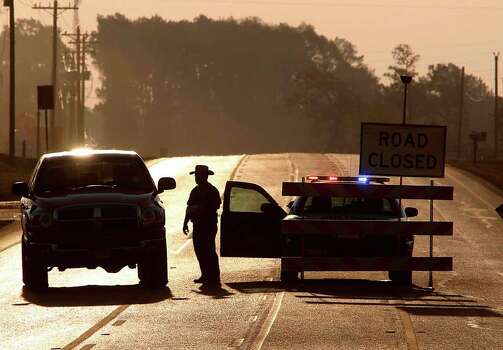 A State Trooper blocks eastbound FM 1488 headed to Magnolia due to wildfires on Saturday, Sept. 10, 2011, in Waller County. Photo: Mayra Beltran, Houston Chronicle / © 2011 Houston Chronicle