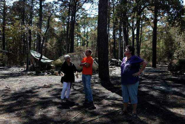 Mindi Morris, right, looks at how high the fire burned the trees in front of her destroyed home as she shows the damage to her best friend, Deborah Rogers, left, and Rogers' son, Jason Sperry, in Circle D Estates on Friday, Sept. 9, 2011. LISA KRANTZ/lkrantz@express-news.net