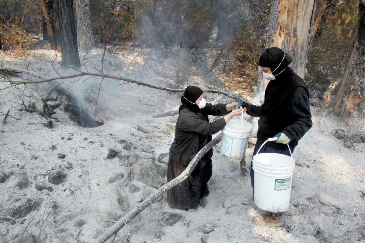 Sister Katerina, right, hands a bucket of water to sister Prodromia, while they and other nuns at St. John the Forerunner Greek Orthodox Monastery, extinguish spot fires around their property, which was threatened the night before by a wildfire near Goldendale, Wash., Thursday, Sept. 8, 2011.