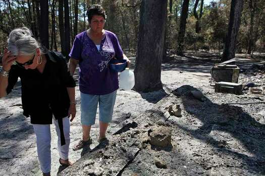 Mindi Morris holds food and water to put out for her eight cats who are missing after the fire destroyed her home, behind her, as she shows her best friend, Deborah Rogers, left, the ruins of her home in Circle D Estates on Friday, Sept. 9, 2011. Morris, who lives with her sister, escaped the fire with six dogs but one dog perished. Their pet pig and goat were rescued by a neighbor but are suffering from smoke inhalation. LISA KRANTZ/lkrantz@express-news.net