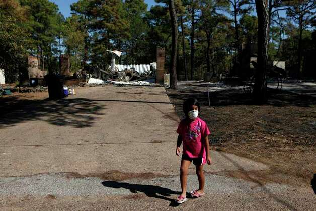 Madalynn Vasquez, 6, walks in front of the two destroyed homes across the street from her home which was not harmed in the Tahitian Village neighborhood in Bastrop on Friday, Sept. 9, 2011. LISA KRANTZ/lkrantz@express-news.net