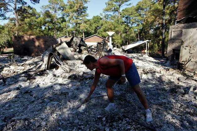 Gina Thurman looks for salvageable items in the ruins of her home where she lived for 10 years in Bastrop on Friday, Sept. 9, 2011. LISA KRANTZ/lkrantz@express-news.net