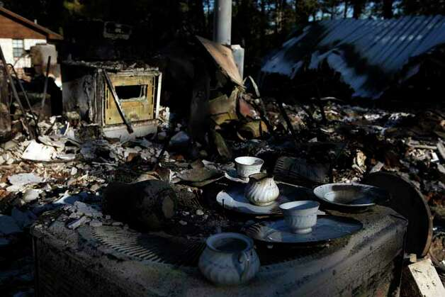 Salvaged tea cups and plates sit on the air conditioning unit amid the ruins of the home owned by the Pierce family on Papaloa Lane in the Tahitian Village neighborhood in Bastrop on Friday, Sept. 9, 2011. LISA KRANTZ/lkrantz@express-news.net