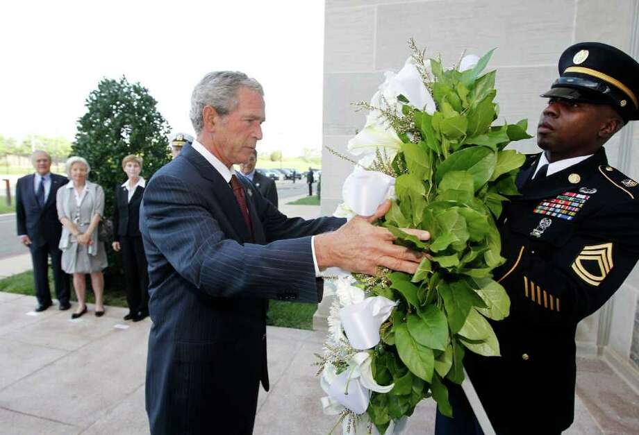 Former President George W. Bush lays a wreath at the Pentagon in Washington in commemoration of the 10th anniversary of the Sept. 11 attacks, Saturday, Sept. 10, 2011. Pictured at rear, left to right: former Defense Secretary Donald Rumsfeld, his wife Joyce Rumsfeld, Deborah Mullen, Chairman of the Joint Chiefs of Staff Adm. Mike Mullen, and Defense Secretary Leon Panetta. (AP Photo/Charles Dharapak) Photo: Charles Dharapak / AP