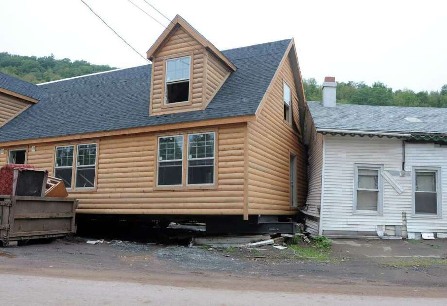 A new log home crashed into another home on  Main St. in Prattsville, N.Y. on Sept. 8, 2011. The Schoharie Creek flooded the town after tropical storm Irene. Photo: Lori Van Buren, Lori Van Buren / Times Union