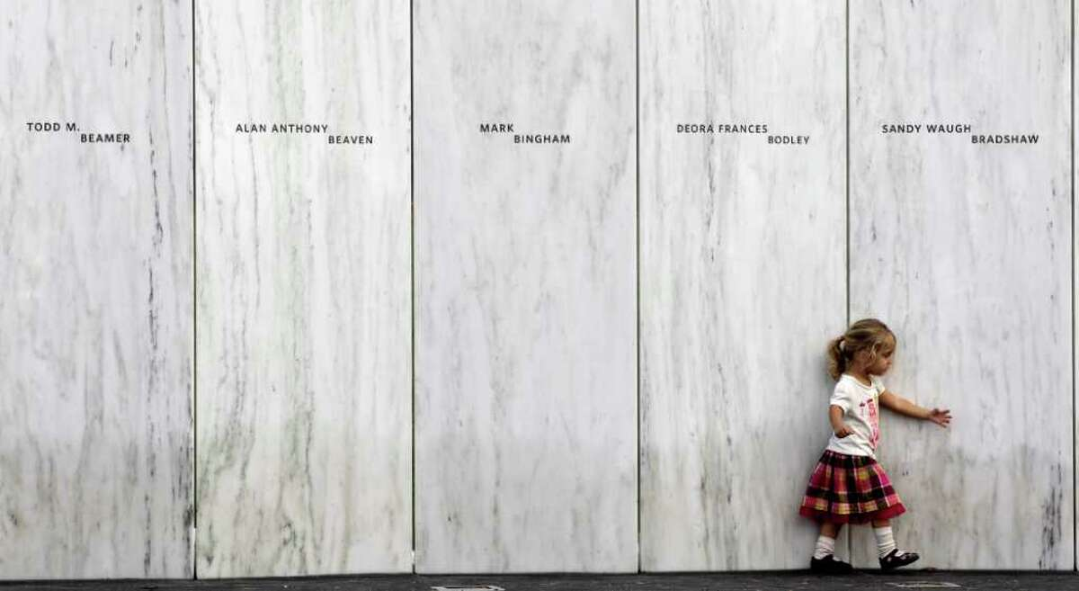 A family member of one of the victims of the crash of United Flight 93 walks along a section of Phase 1 of the permanent National Memorial following its dedication, near the crash site of Flight 93 in Shanksville, Pa., Saturday, Sept. 10, 2011. The names of the 40 victims of the crash are inscribed on the marble panels. (AP Photo/Amy Sancetta)