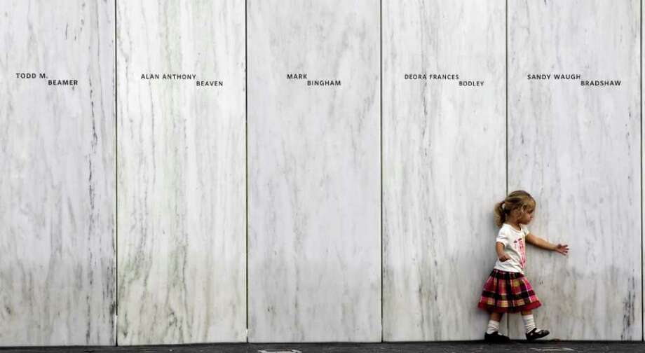 A family member of one of the victims of the crash of United Flight 93 walks along a section of Phase 1 of the permanent National Memorial following its dedication, near the crash site of Flight 93 in Shanksville, Pa., Saturday, Sept. 10, 2011.   The names of the 40 victims of the crash are inscribed on the marble panels. (AP Photo/Amy Sancetta) Photo: Amy Sancetta, Associated Press / AP2011