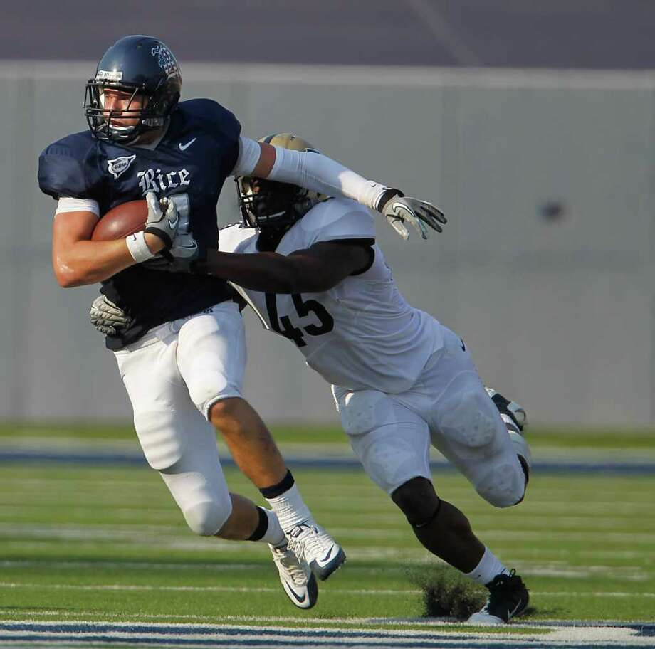 Rice WR Randy Kitchens (4) runs the ball as he gets tackled by Purdue LB Will Lucas (45) during the fourth quarter of a college football game at Rice University, Saturday, Sept. 10, 2011, in Houston. Rice won the game against Purdue 24-22. Photo: Karen Warren, Houston Chronicle / © 2011 Houston Chronicle