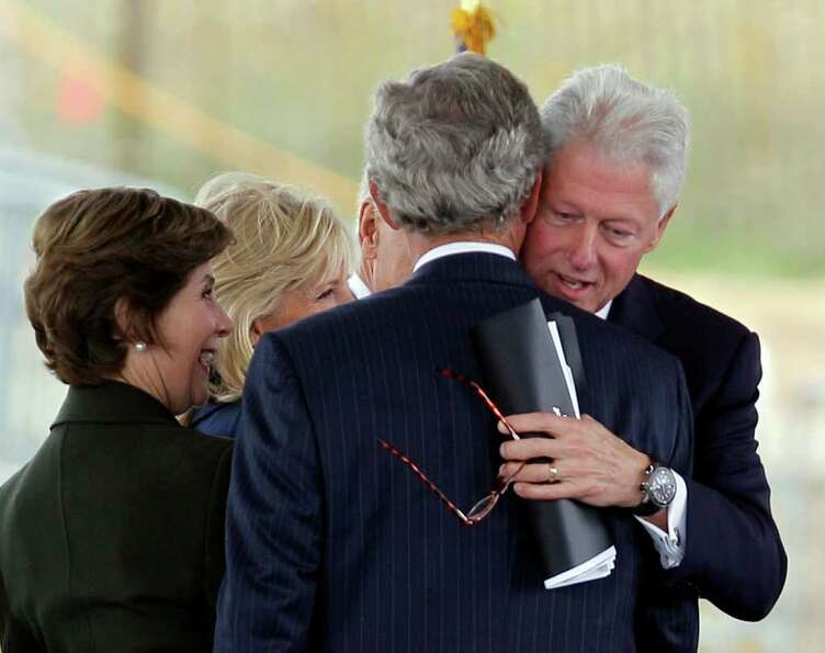 Former President Bill Clinton hugs former President George W. Bush after speaking  during the dedica