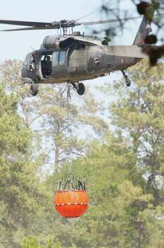 A Black Hawk hovers over a pond as it fills up with water to drop on a fire line. Photo: Mayra Beltran, Houston Chronicle / © 2011 Houston Chronicle
