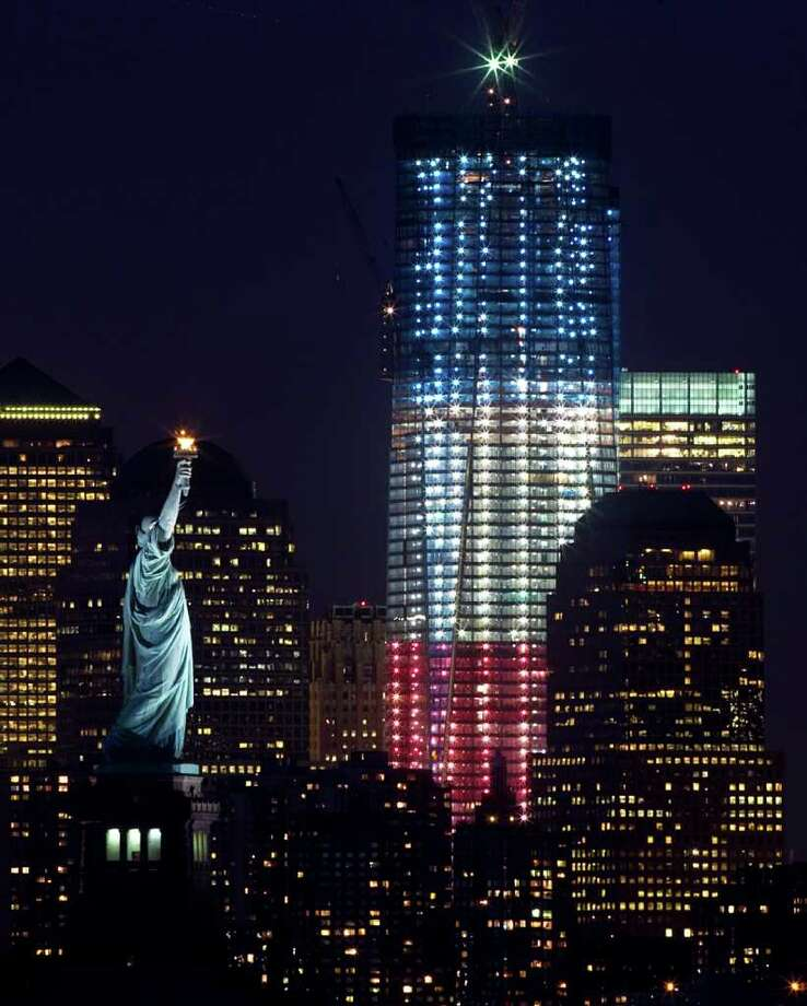 One World Trade Center (formerly known as the Freedom Tower) at Ground Zero is lit up red, white and blue for the 10th Anniversary of 9-11, as it is seen with the Statue of Liberty in New York, Friday, September 9, 2011. After it's expected completion in 2013, it will be the tallest building in the United States standing at 1,776 feet. Photo: Tom Fox, McClatchy-Tribune News Service / Dallas Morning News