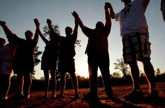 Participants raise their hands in prayer. Photo: Mayra Beltran, Houston Chronicle / © 2011 Houston Chronicle