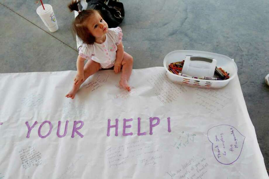 """Madylynne Williams sits on a banner made at a prayer rally at Unity Park. It says, """"We Appreciate Your Help!"""" It will be taken to firefighters headquarters in Magnolia. Photo: Mayra Beltran / © 2011 Houston Chronicle"""
