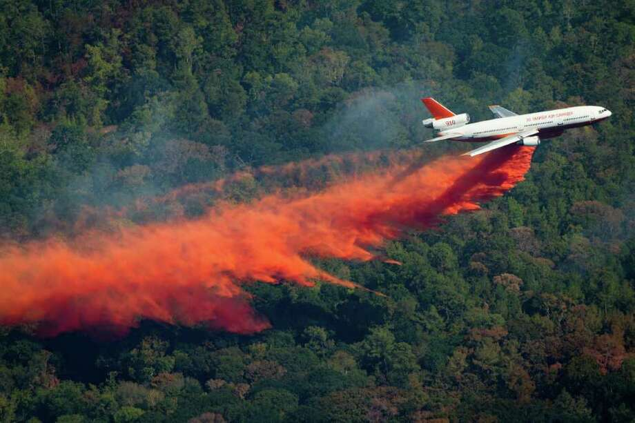 SMILEY N. POOL : CHRONICLE BATTLE FROM ABOVE: A DC-10 drops retardant to help fight a large wildfire Saturday near Magnolia. The air tanker made six runs over the fast-moving wall of flames, dumping more than 11,000 gallons of fire retardant in each pass. Photo: Smiley N. Pool / © 2011  Houston Chronicle