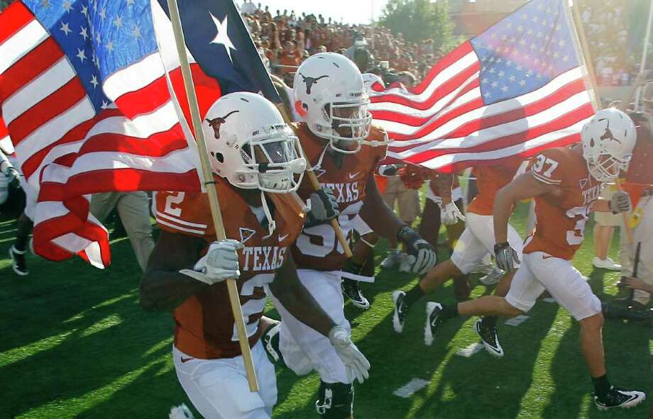 Texas players carry U.S. flags before beating BYU on Saturday. Photo: Eric Gay, Associated Press / AP