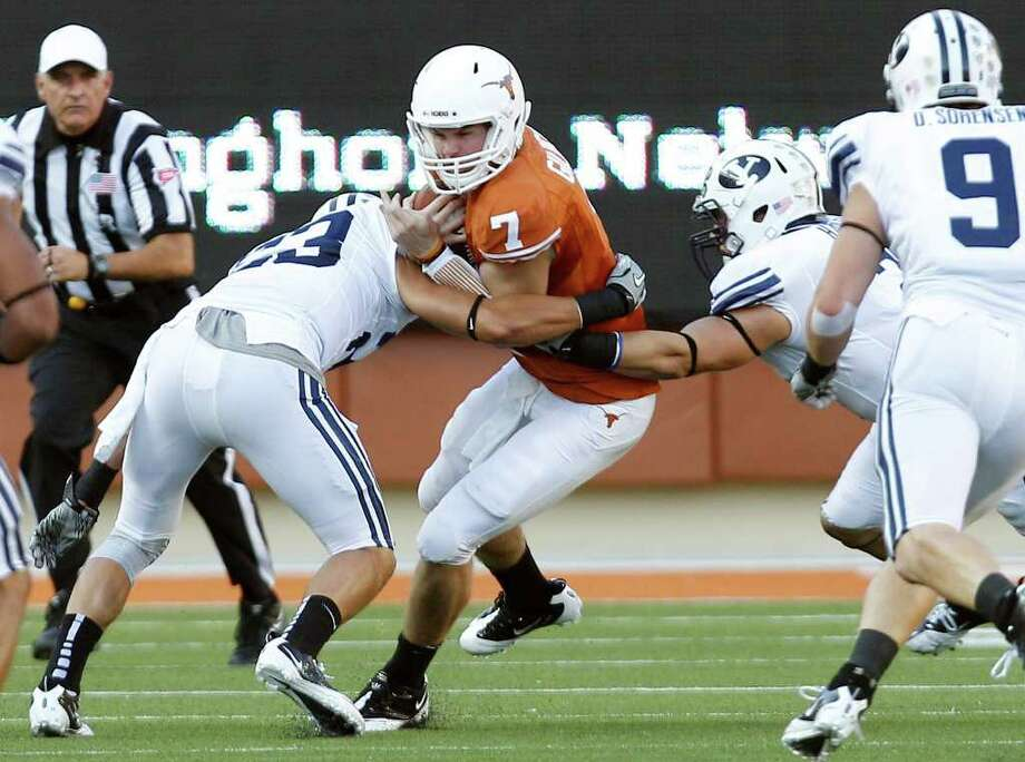 Texas' Garrett Gilbert (7) is hit by BYU's Travis Uale, left, during the first quarter an NCAA college football game, Saturday, Sept. 10, 2011, in Austin, Texas. (AP Photo/Eric Gay) Photo: Eric Gay, Associated Press / AP