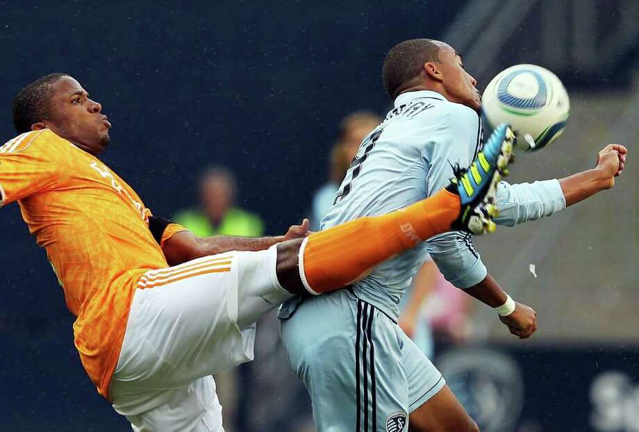 Teal Bunbury of Sporting Kansas City takes it on the chin as the Dynamo's Jermaine Taylor connects during Saturday's game. Photo: Jamie Squire / 2011 Getty Images