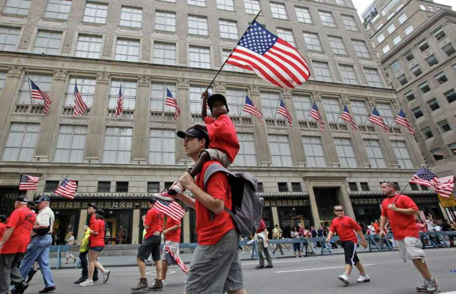 Duke Scoppa, a prop master with Local 52, marches up Fifth Ave with his Haitian-born son Erickson Scoppa, 5, during the Labor Parade Saturday, Sept. 10, 2011 in New York.  Members of hundreds of unions are honoring labor by marching in a New York City parade laced with remembrances of the Sept. 11 attacks. (AP Photo/Mary Altaffer) Photo: Mary Altaffer
