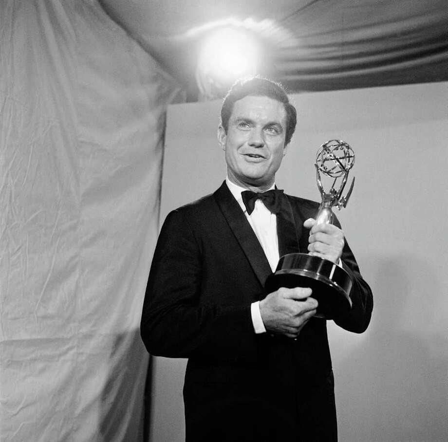 "FILE - In this May 22, 1966 file photo, actor Cliff Robertson holds the Emmy he won for the outstanding single performance by an actor in a leading role in a drama at the 18th annual Television Academy Awards in the Hollywood section of Los Angeles. Robertson, the movie actor who played John F. Kennedy in ""PT-109,"" won an Oscar for ""Charly"" and was famously victimized in a 1977 Hollywood forgery scandal, died Saturday, Sept. 10, 2011. He was 88. (AP Photo)"