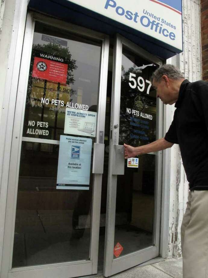 In this photo taken Wednesday Sept. 7, 2011, William Scott, 79, enters a post office to mail a letter in Worthington, Ohio. Scott said he usually visits the post office three times a week to send mail. If the local post office were to shut own, would anyone miss it? Yes, many people are saying as the U.S. Postal Service is desperate to streamline its operations and save money. (AP Photo/Kantele Franko) Photo: Kantele Franko