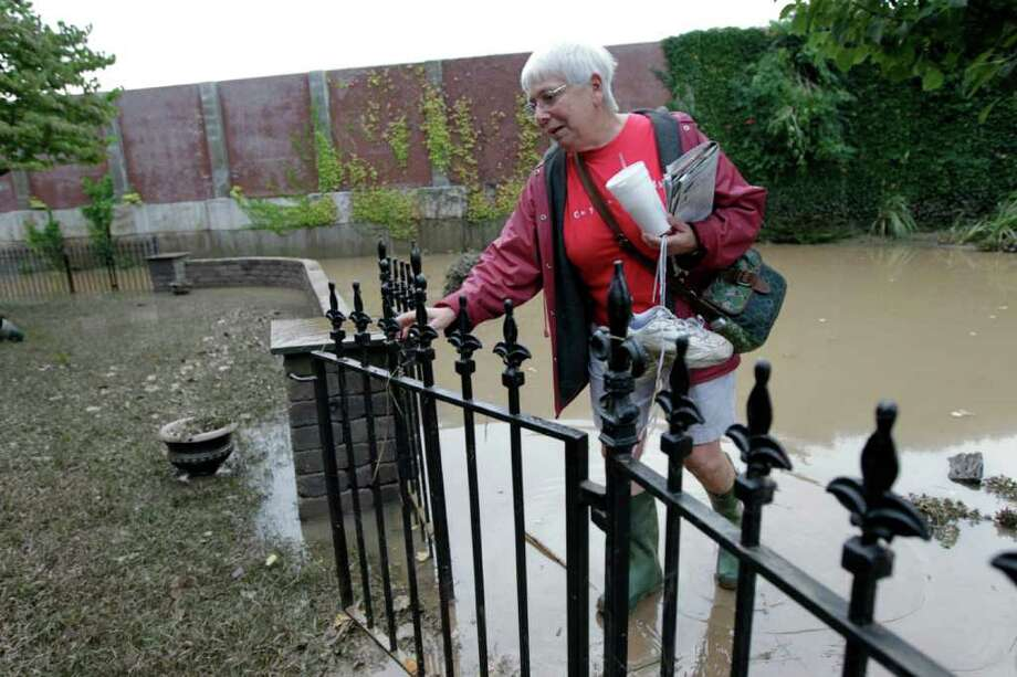 Ellie Martindale, one of the first residents to return, walks in her gate to check on her home after flooding in the Shipoke area caused by the remnants of Tropical Storm Lee Saturday, Sept. 10, 2011 in Harrisburg, Pa. (AP Photo/Alex Brandon) Photo: Alex Brandon
