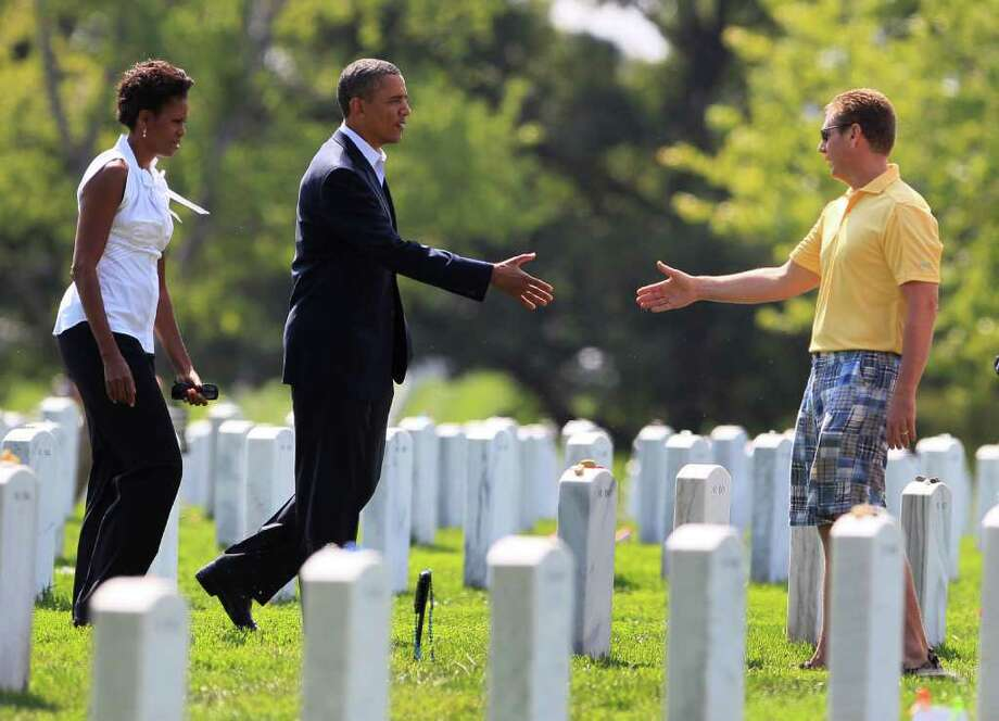 President Barack Obama extends a hand to an unidentified visitor to Section 60 in Arlington National Cemetery Saturday, Sept. 10, 2011, in Arlington, Va., as he and first lady Michelle Obama, left, pay their respects to those who have made the ultimate sacrifice over the past decade. Sunday will mark the 10th anniversary of the Sept. 11 attacks. (AP Photo/Carolyn Kaster) Photo: Carolyn Kaster