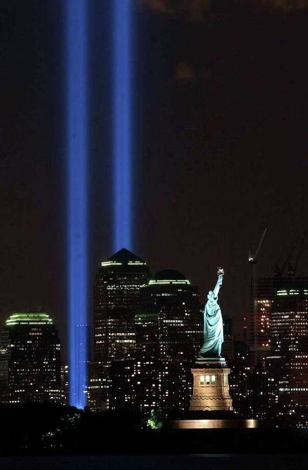 In this Sept. 11, 2004 file photo, the Tribute in Light shines over the Manhattan skyline and the Statue of Liberty in New York, on the anniversary of the terrorist attacks on the World Trade Center. The memorial was first presented on March 11, 2002, the six-month anniversary of the attacks, and has been presented by the Municipal Art Society every year since. (AP Photo/Brian Branch-Price, File) Photo: Brian Branch-Price / AP2004