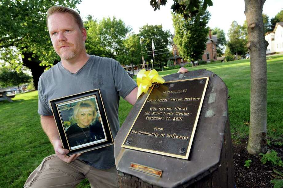 "Frank Tatum holds a picture and kneels by a memorial of his mother, Diane ""Dani"" Moore Parsons, on Friday, Sept. 2, 2011, at Blockhouse Park in Stillwater, N.Y. Parsons, a Stillwater native and State Department of Taxation and Finance worker, was killed on Sept. 11, 2001 at the World Trade Center. (Cindy Schultz / Times Union) Photo: Cindy Schultz"