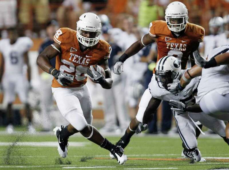 Texas' Malcolm Brown (28) runs for a first down during the fourth quarter on an NCAA college footbal