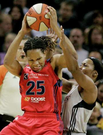 Mystics' Monique Currie, left, is blocked by Silver Stars' Jia Perkins during the first half of a WNBA basketball game, Saturday, Sept. 10, 2011, in San Antonio. Photo: Darren Abate, Express-News