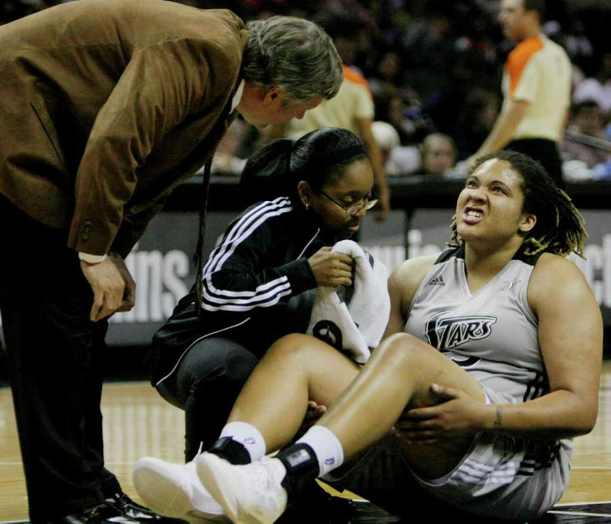 Silver Stars head coach Dan Hughes, left, looks on as Stars' Danielle Adams, right, is checked out after suffering an injury during the first half of a WNBA basketball game against the Washington Mystics, Saturday, Sept. 10, 2011, in San Antonio.