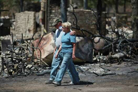 "Linda Strong and her husband of 55 years, Jerry Strong, walk around their destroyed home, where they lived for 18 years, in Bluebonnet Acres which was burned by the Union Chapel Fire on the west side of Bastrop on Saturday, Sept. 10, 2011. Although residents had been let in to one section of the neighborhood, most residents were only allowed back for the first time starting at 10 am Saturday. ""We look at the bright side. You count your blessings,"" Linda said. Photo: LISA KRANTZ, LISA KRANTZ/lkrantz@express-news.net / SAN ANTONIO EXPRESS-NEWS"