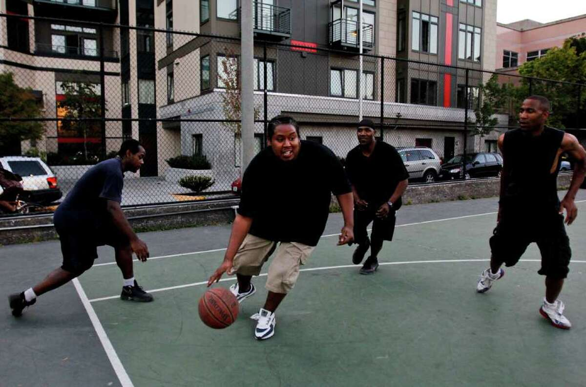 Left to right; Horace, Charles Hunter, Condel Walker, and Tony play basketball at Cal Anderson Park.