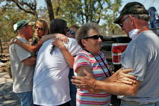 Nancy Thomas, of Pharr, says goodbye to her brother, Jerry Strong, far right, after spending the morning together with several family members looking for salvageable items in the Strong's destroyed home in Bluebonnet Acres, which was burned by the Union Chapel Fire on the west side of Bastrop, on Saturday, Sept. 10, 2011. Although residents had been let in to one section of the neighborhood, most residents were only allowed back for the first time starting at 10 am Saturday. From left, Robin Thomas, of Beeville, hugs the Strong's son, Tim Strong, of Grass Valley, CA, while Linda Strong gets a hug from her nephew and Robin's husband, Dan Thomas. Photo: LISA KRANTZ, LISA KRANTZ/lkrantz@express-news.net / SAN ANTONIO EXPRESS-NEWS