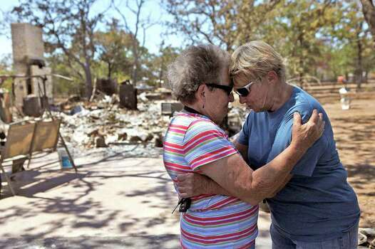 Linda Strong, right, says goodbye to her sister-in-law, Nancy Thomas, of Pharr, after spending the morning together with several family members looking for salvageable items in Strong's destroyed home in Bluebonnet Acres, which was burned by the Union Chapel Fire on the west side of Bastrop, on Saturday, Sept. 10, 2011. Although residents had been let in to one section of the neighborhood, most residents were only allowed back for the first time starting at 10 am Saturday. Photo: LISA KRANTZ, LISA KRANTZ/lkrantz@express-news.net / SAN ANTONIO EXPRESS-NEWS