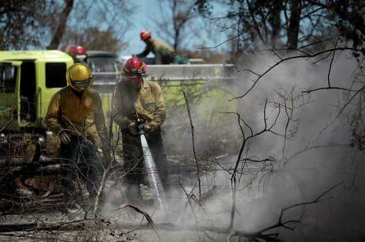 Bureau of Land Management Firefighters from Winnemucca, NV including John Strickler, left, and Kory Bowser, right, work to put out a hot spot they've been monitoring in Bluebonnet Acres which was burned by the Union Chapel Fire on the west side of Bastrop on Saturday, Sept. 10, 2011. Photo: LISA KRANTZ, LISA KRANTZ/lkrantz@express-news.net / SAN ANTONIO EXPRESS-NEWS