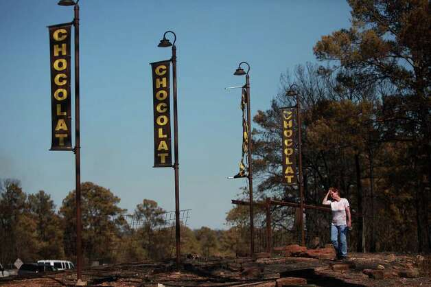 Roselly Hendriks walks in front of her destroyed home and business, Roscar Chocolate, owned by she and her husband, Frans Hendriks, as they wait for Governor Rick Perry to arrive, who was scheduled to speak at a press conference at their business on Hwy 71 which opened for the first time on Saturday morning for thru traffic only, in