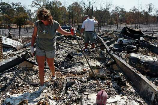 Sherri Edwards and her husband, Dayne Edwards, look for salvageable items in the ruins of their home of 14 years in Bluebonnet Acres, which was burned by the Union Chapel Fire on the west side of Bastrop, on Saturday, Sept. 10, 2011. Saturday was the first day they and their neighbors were allowed to re-enter their section of the neighborhood and see their homes for the first time since the fire. Photo: LISA KRANTZ, LISA KRANTZ/lkrantz@express-news.net / SAN ANTONIO EXPRESS-NEWS