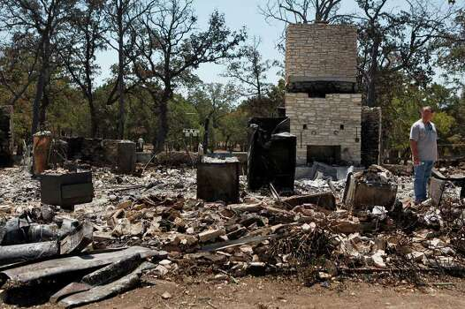 Larry Pounds, of Austin, looks at the ruins of the home owned by his in-laws, Linda and Jerry Strong, in Bluebonnet Acres which was burned by the Union Chapel Fire on the west side of Bastrop on Saturday, Sept. 10, 2011. Although residents had been let in to one section of the neighborhood, most residents were only allowed back for the first time starting at 10 am Saturday. Photo: LISA KRANTZ, LISA KRANTZ/lkrantz@express-news.net / SAN ANTONIO EXPRESS-NEWS