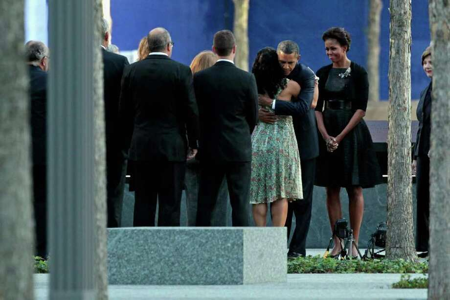 NEW YORK, NY - SEPTEMBER 11:  U.S. President Barack Obama (2nd R) embraces victims' family members as first lady Michelle Obama (R) stands by at the 9/11 Memorial during the tenth anniversary ceremonies of the September 11, 2001 terrorist attacks at the World Trade Center site, September 11, 2011 in New York City. New York City and the nation are commemorating the tenth anniversary of the terrorist attacks on lower Manhattan which resulted in the deaths of 2,753 people after two hijacked planes crashed into the World Trade Center.  (Photo by Chip Somodevilla/Getty Images) Photo: Chip Somodevilla, Getty / 2011 Getty Images