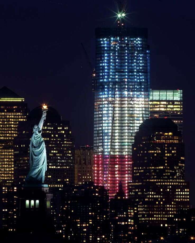 In this Friday, Sept. 9, 2011 photo, One World Trade Center, formerly known as the Freedom Tower, at ground zero is lit up red, white and blue for the 10th anniversary of the 9/11 terrorist attacks, as the Statue of Liberty is seen at left, in New York. (AP Photo/The Dallas Morning News, Tom Fox)  MANDATORY CREDIT; MAGS OUT; TV OUT; INTERNET OUT; AP MEMBERS ONLY Photo: AP
