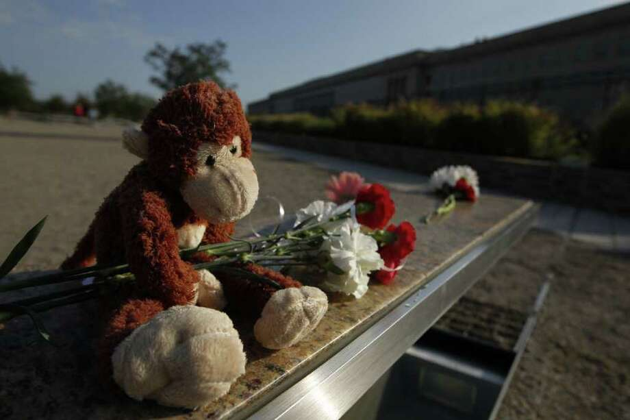 A stuffed toy and flowers are left on the bench for Dana Falkenberg, from University Park, Md., who was three when she died on American Flight 77 when it crashed into the Pentagon, at the Pentagon Memorial ahead of the 10th anniversary of the Sept. 11 attacks, Saturday, Sept. 10, 2011. Photo: AP
