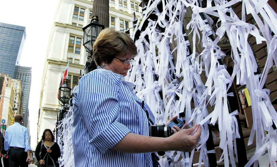 Cheryl Hickman, of Pikeville, Ky., examines many of the ribbons with inspirational and personal messages tied along the fence line of St. Paul's Chapel on Broadway, two blocks from the World Trade Center site, on Saturday, Sept. 10, 2011, in New York, as officials prepare for the 10th anniversary of the 9/11 attacks. (AP Photo/The Dallas Morning News, Louis DeLuca)  MANDATORY CREDIT; MAGS OUT; TV OUT; INTERNET OUT; AP MEMBERS ONLY Photo: AP